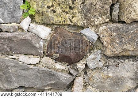 Old Stone Wall With Grass And Moss In Cement Joints