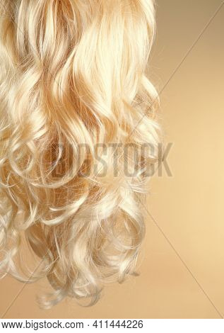 Blond Hair. Beautiful healthy long curly blonde hair close-up texture. Dyed Wavy white hair background, coloring, extensions, cure, treatment concept. Over green backdrop. Haircare.