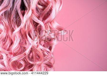 Hair. Beautiful healthy long curly dyed pink color hair close-up texture. Fashion trendy Dyed wavy hair background, coloring, extensions, cure, treatment concept. Haircare