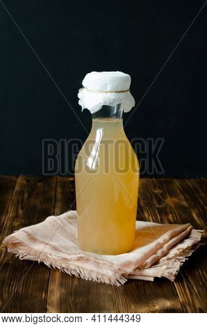 Ginger And Lemon Drink - Kombucha In A Bottle On A Dark Wooden Background. Ginger Ale Is A Homemade