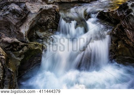 Small Waterfall Of A Fast And Crystalline Mountain River, On A Bedrock, Long Exposure With Silk Effe