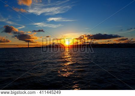 Sunset Over The Tagus River In Lisbon . Ponte 25 De Abril In The Twilight