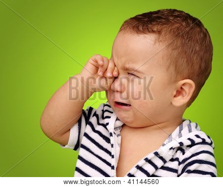 Portrait Of Baby Boy Crying against a green background poster