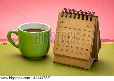 July 2021 - spiral desktop calendar against abstract paper landscape with a cup of coffee, time and business concept