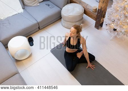 Beautiful Blonde Woman Doing Home Workout Indoors. Woman Practice Yoga At Home. Fit Girl Using Worko