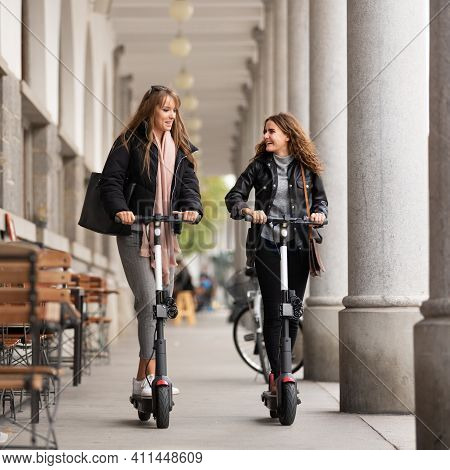 Trendy Fashinable Teenager Girls Riding Public Rental Electric Scooters In Urban City Environment. N
