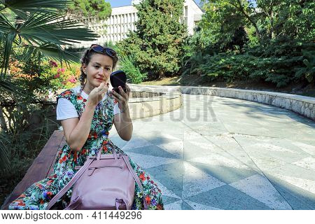 Young Woman In Summer Dress Sits On Bench In Deserted Park, Looks At Face In Mirror And Checks Makeu