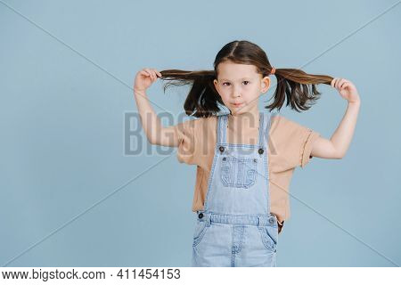 Cute Little Girl Pulling Her Ponytails To Sides, Posing For A Photo Over Blue Background. She Wears