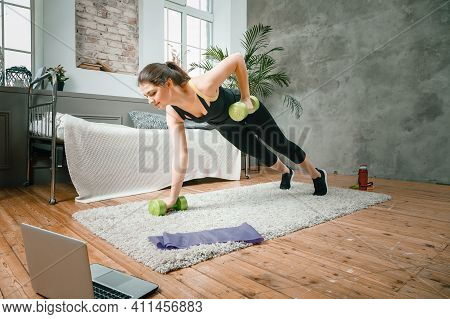 The Young Woman Goes In For Sports At Home. Cheerful Sportswoman With Black Hair Stands In The Bar A