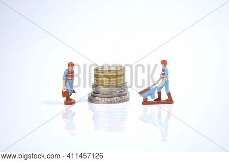 Selective Focus Image Of Working Person Miniature With Stack Of Coins On A White Background. Life Co