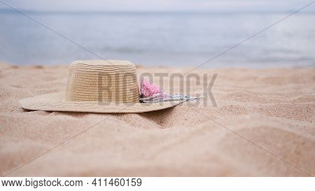 Travel Summer Holidays Concept. Hat On Sand Beach At Coast With Blur Blue Sea. Women Is Fashion For
