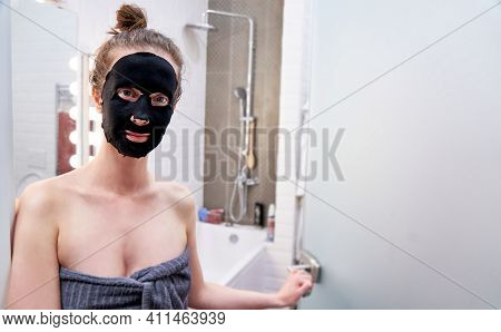Woman facial skin care. Woman in black regenerating collagen cosmetic beauty mask at home.