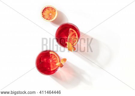 Negroni Cocktails With Blood Oranges, Overhead Flat Lay Shot On A White Background, With Shadows And