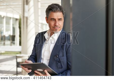 Confident elegant older businessman in suit standing and working with business tablet computer in office atrium.