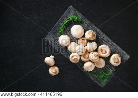 Raw Mushrooms Champignons On A Wooden Board On A Black Background. Top View. Cooking Champignons.