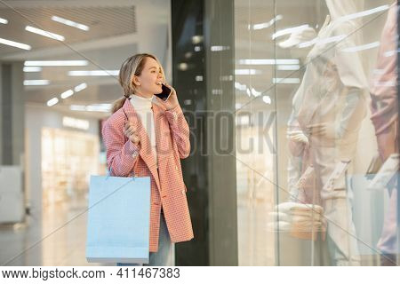 Young woman with shopping bags talking on mobile phone and looking at shop window during her shopping in the mall