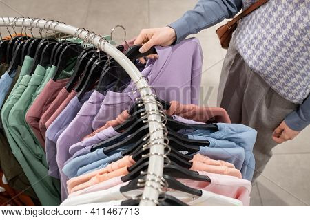 Close-up of woman choosing shirt on the rack for herself in clothing store