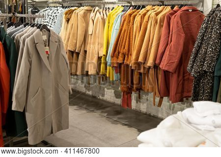 Image of fashion clothes hanging on the rack in modern clothing store