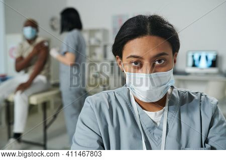 Young serious mixed-race female clinician in uniform and protective mask standing in front of camera against her colleague vaccinating patient