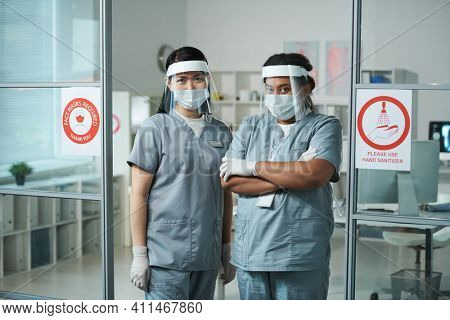 Two young intercultural female clinicians in protective workwear standing in front of camera against medical office interior in modern clinics