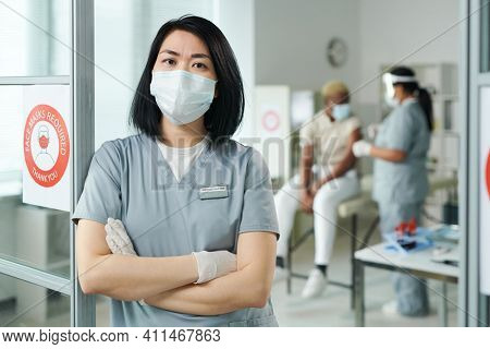 Young cross-armed female clinician in protective workwear standing in front of camera while her colleague vaccinating one of patients
