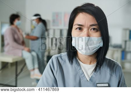 Young serious Asian female clinician in uniform and protective mask standing in front of camera against her colleague vaccinating patient