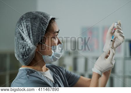 Young serious nurse of Asian ethnicity in protective workwear preparing injection for patient in medical office of contemporary clinics