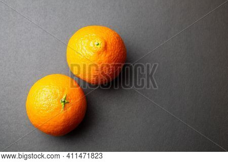 Tangerines On A Black Background. Two Orange Tangerines Lie On The Table. Close-up.