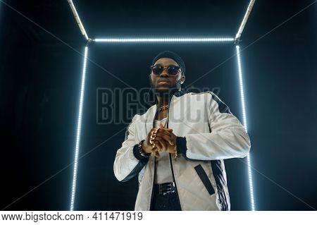 Stylish rapper in sunglasses, dark background