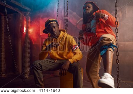 Two stylish rappers dancing in studio