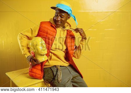 Stylish rapper poses in studio with yellow tones