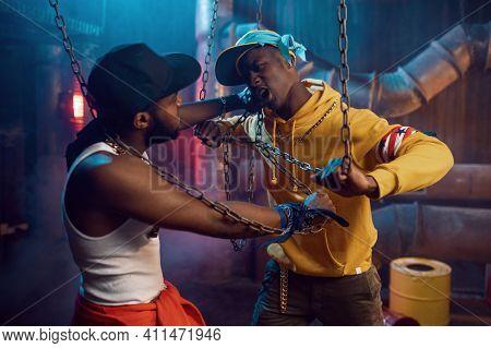 Two rappers posing, performing in studio