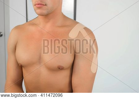 Kinesiology Tapes On Mans Shoulder And Hand For Fixation Of Muscles, Closeup Body. Using Of Tapes In