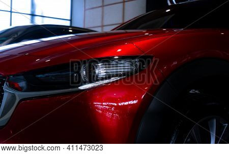 Closeup Headlight Of Shiny Red Luxury Suv Car In Showroom. Elegant Electric Car With Sport Design. C