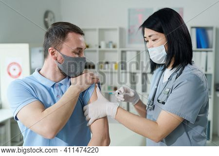 Female clinician or nurse of Asian ethnicity in uniform and protective mask making injection to young man sitting in front of her in medical office