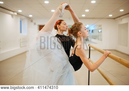 Teacher rehearsing with young ballerina at barre