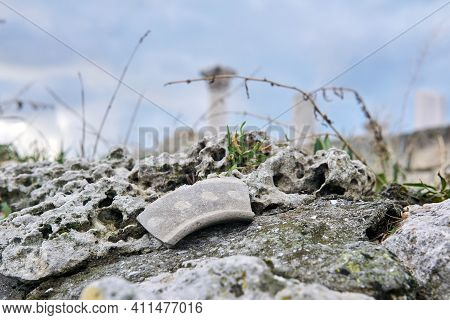 Shard Of Ancient Ceramics On A Stone Among The Grass Against A Background Of Blurry Ancient Ruins