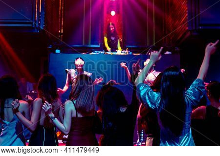 Group Of People Dance In Disco Night Club To The Beat Of Music From Dj On Stage . New Year Night Par