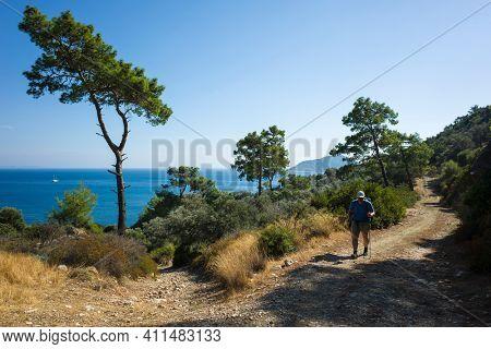 Hiking Lycian way. Man is trekking on dirt road along Mediterranean sea coast, Outdoor activity in Turkey. (stretch from Patara to Kalkan)