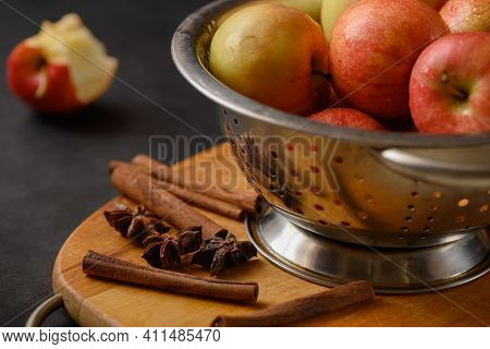 Metallic Bowl Full Of Red Ripe Apples On Wooden Cutting Board With Scattered Cinnamon Sticks With On