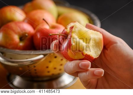 Bitten Apple In Human Hand On Metallic Bowl Full Of Red Ripe Apples Background. Healthy Eating. Appl