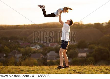 Father And Daughter Have Fun Together. Dad Throws His Daughter Up In Sky