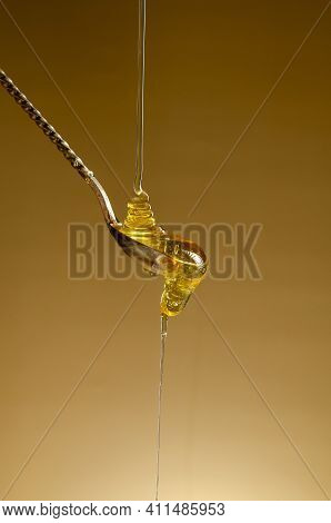 Spoon With A Pouring Drop Of Golden Honey On Yellow Background.