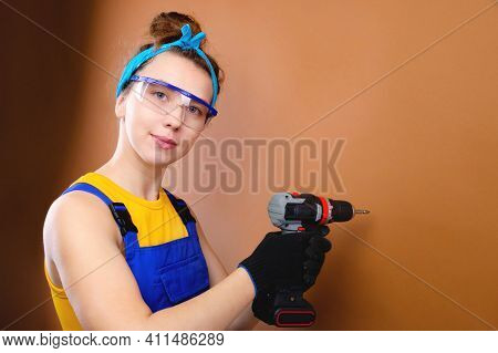 Attractive Young Woman In Overalls Overalls And Goggles With A Screwdriver In Her Hand On A Brown Ba