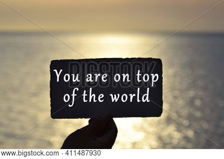 You Are On Top Of The World Text On Hand Holding Torn Paper With Blurred Background Of Sunset At The
