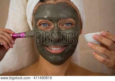An adult beautiful woman in a bathroom and a towel takes care of her skin and applies a clay mask to her face