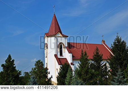 St. Joseph's Roman Catholic Church Against Blue Sky.  Church Is Built In  Gothic Style. The Walls Of