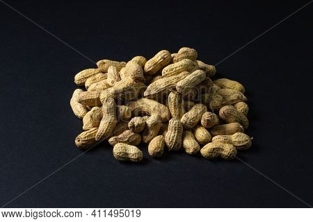 Peanuts On A Black Background. Small Pile Of Peanuts On A Dark Background. Peanuts In Shell