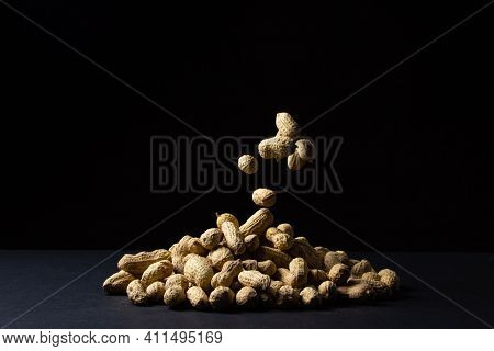 Peanuts On A Black Background. A Peanut Falls On A Pile Of Peanuts. Peanuts In Shell