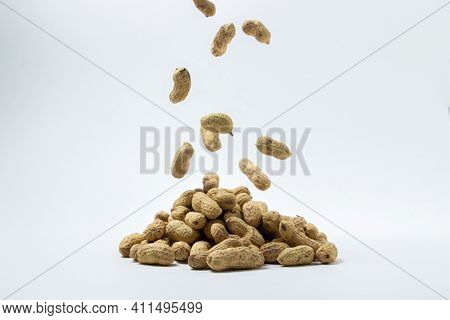 Peanuts On A White Background. A Peanut Falls On A Pile Of Peanuts. Peanuts In Shell